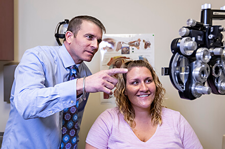 Dr Greene giving an eye exam to a patient